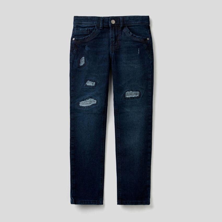 Jeans slim fit de aparência desgastada